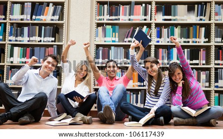 Happy group of students at the library with arms up - stock photo