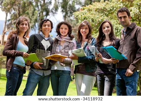 Happy group of students outdoors holding notebooks - stock photo