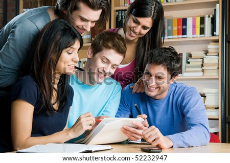 Happy group of students studying and working together in a college library - stock photo