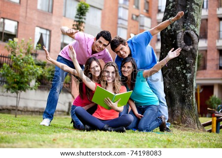 Happy group of students with arms up outdoors