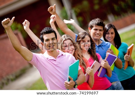 Happy group of students with arms up outdoors - stock photo