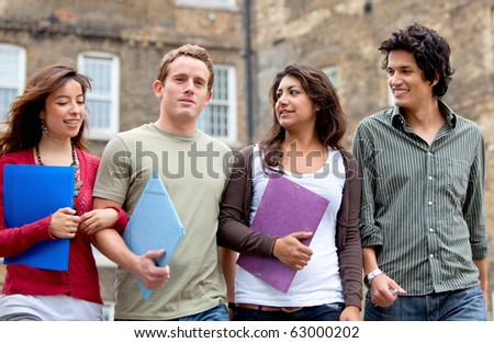 Happy group of students with notebooks walking outdoors - stock photo