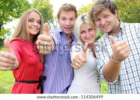 Happy group of students with thumbs up - outdoors