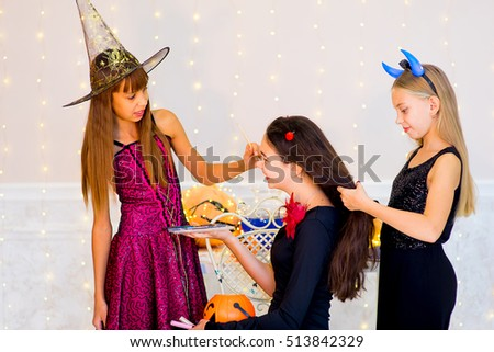Happy group of teenagers in costumes preparing for Halloween, near the table with pumpkins and bottle of potion