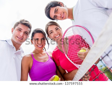 Happy group of tennis players holding rackets outdoors