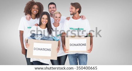 Happy group of volunteers holding clothes donation boxes against grey vignette