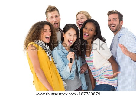 Happy group of young friends having fun doing karaoke on white background - stock photo