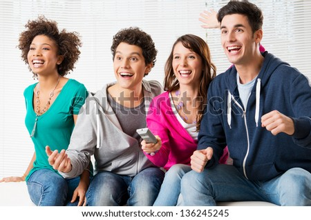 Happy Group Of Young Friends Watching Television And Supporting Their Team - stock photo
