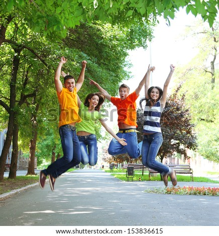 Happy group of young people jumping in park - stock photo