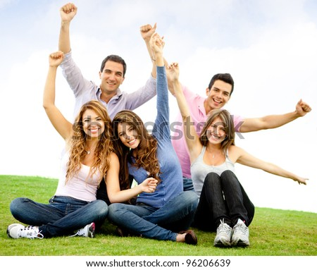Happy group of young people with arms up - outdoors - stock photo
