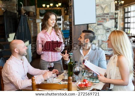 Happy group people having dinner at rural restaurant. Focus on the waiter - stock photo
