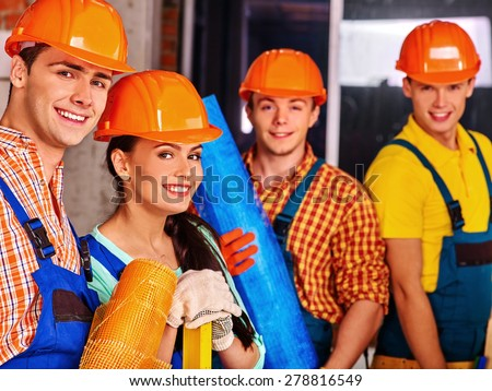 Happy group people in builder uniform. Four people. - stock photo