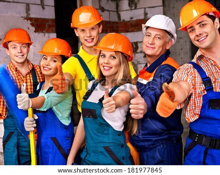 Happy group people in builder uniform thumb up. - stock photo