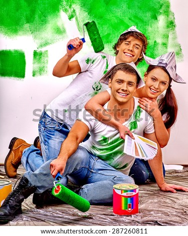 Happy group people of three person paint wall at home. - stock photo