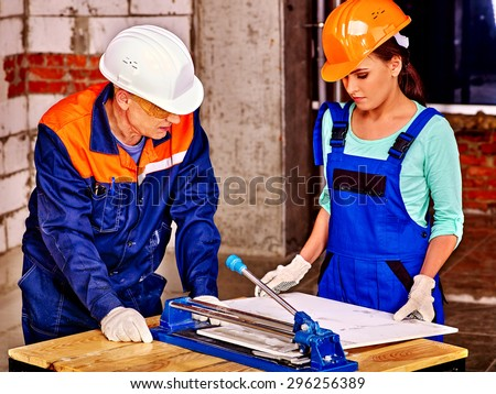 Happy group people old man and young woman builder cutting ceramic tile. - stock photo