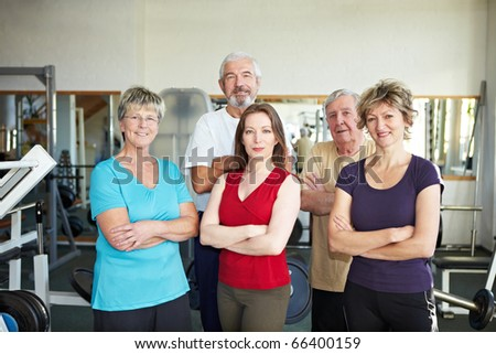 Happy group with arms crossed in a gym - stock photo