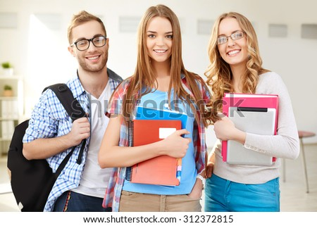 Happy groupmates in casualwear looking at camera - stock photo