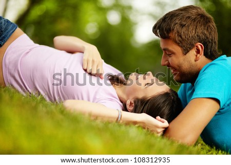 Happy guy and girl spending time together in park enjoying each other�s company - stock photo