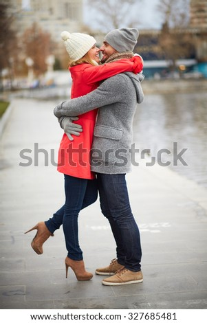 Happy guy and his girlfriend embracing in urban environment - stock photo