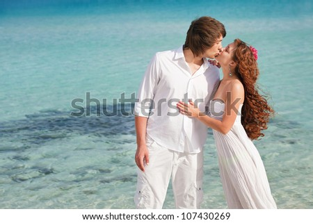Happy guy and the girl kiss on a beach. a young pair on the seashore