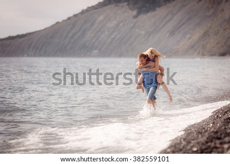 happy guy and the girl running along the beach  - stock photo