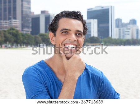Happy guy in a blue shirt with cityscape in the background - stock photo
