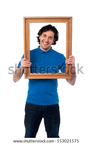 Happy guy looking through empty picture frame - stock photo