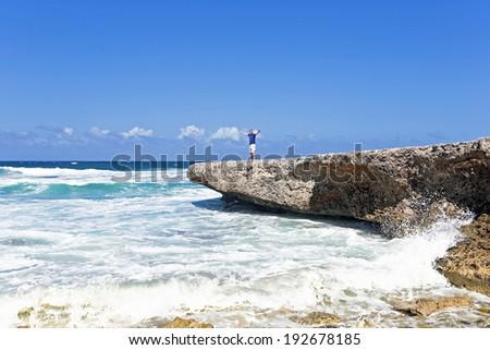 Happy guy on the rocks on Aruba island in the Caribbean - stock photo