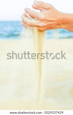 happy guy pours sand from the sea of hands