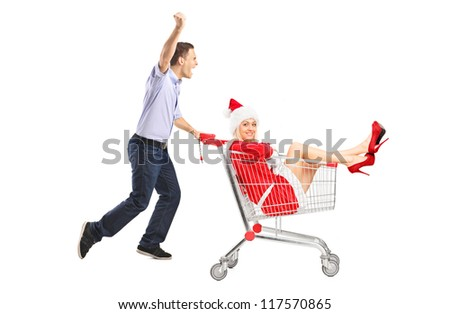 Happy guy pushing a shopping cart and female in christmas costume isolated on white background