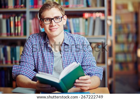 Happy guy sitting in library with interesting book - stock photo