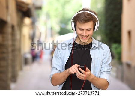 Happy guy walking and using a smart phone to listen music with headphones - stock photo