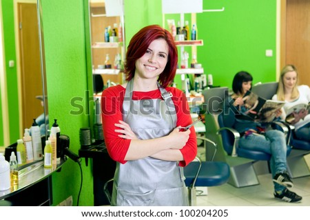 Happy hair salon owner or employee with customers in the background - stock photo