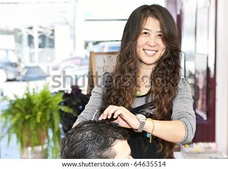 Happy hairdresser cutting hair in her salon - stock photo