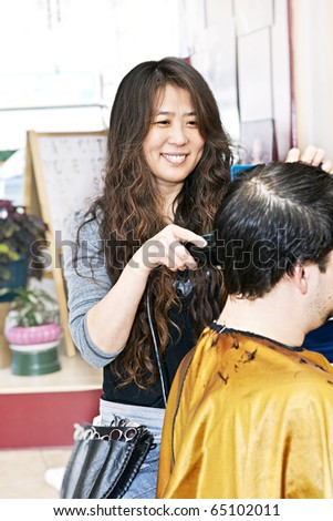 Happy hairdresser cutting hair in her salon - stock photo