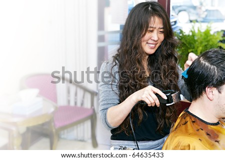 Happy hairdresser cutting hair in her salon with copy space - stock photo