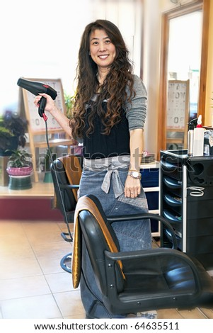 Happy hairdresser holding hairdryer in hair salon - stock photo