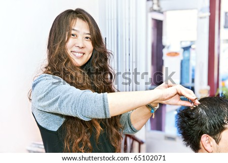 Happy hairstylist cutting hair in her salon - stock photo