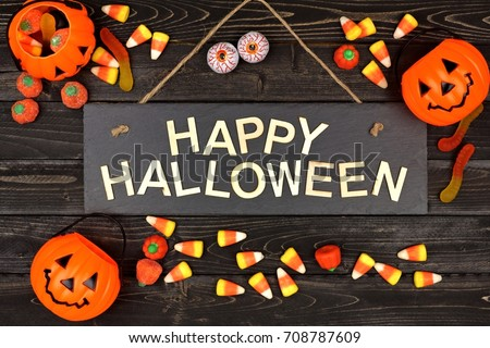 Happy Halloween Black Sign With Wood Letters And Frame Of Candy On A Black  Wood Background