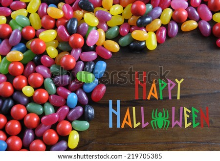 Happy Halloween candy on rustic dark wood background with sample text message greeting. - stock photo