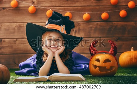 Happy Halloween! Cute cheerful little witch with a book of spells. Beautiful child girl in witch costume sitting on grass, reading and laughing.