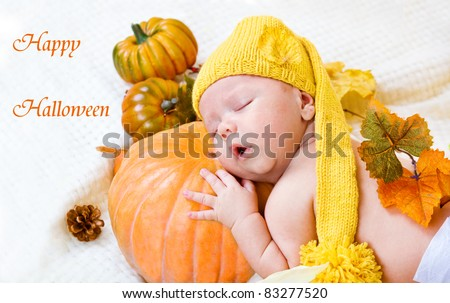 Happy Halloween greeting card with baby sleeping on a pumpkin - stock photo