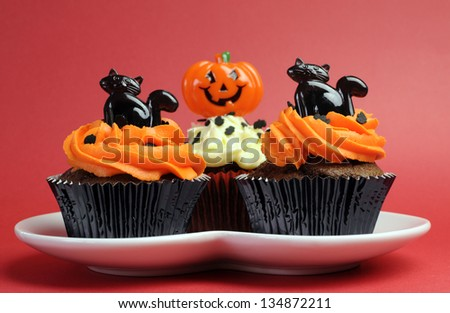 Happy Halloween orange and black decorated cupcakes with black cats and jack-o-lanterns on white heart plate against a red background. - stock photo
