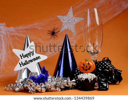 Happy Halloween party decorations with cobweb and spider, champagne glass, hats, chocolate cupcake, stars and streamers on orange background. - stock photo