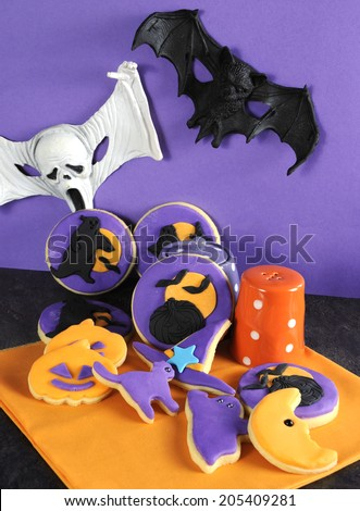 Happy Halloween party trick or treat purple and orange cookies with pumpkins, cats, ghost, moon, and witches hat with ghoul and bat decorations. - stock photo