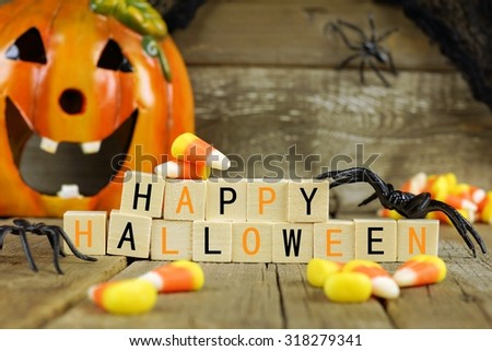 Happy Halloween wooden blocks with candy corn and decor against an old wood background - stock photo
