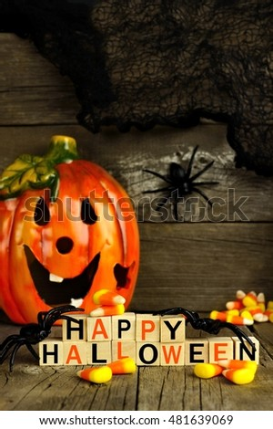 Happy Halloween wooden blocks with jack o lantern and decor against an old wood background