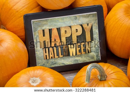 Happy Halloween - word abstract in letterpress wood type on a digital tablet surrounded by pumpkins - stock photo