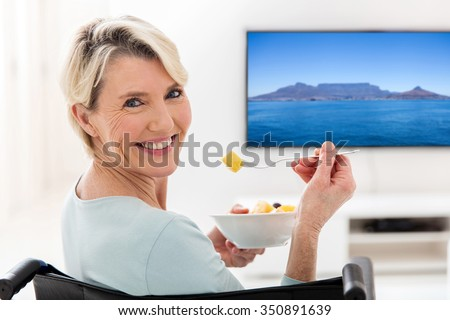 happy handicapped elderly woman eating fruit salad at home - stock photo