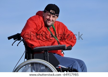 Happy handicapped man on a wheelchair over a green meadow - stock photo